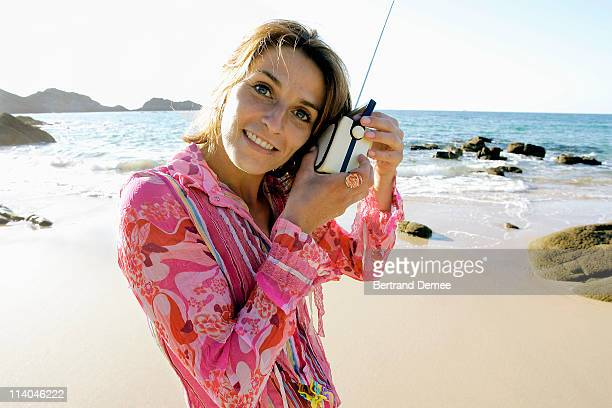 girl  listens to a retro radio at the beach