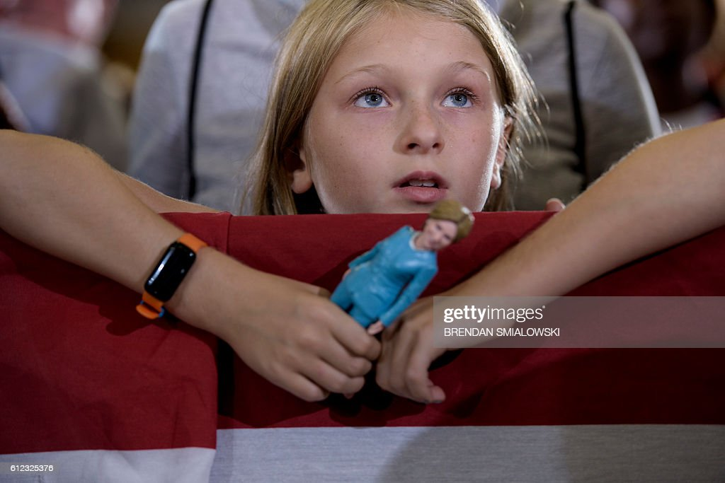A girl listens while Democratic presidential nominee Hillary Clinton speaks during an Ohio Democratic Party rally October 3, 2016 in Akron, Ohio. / AFP / Brendan Smialowski