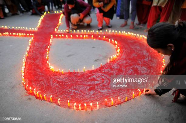 A girl lit candles around the symbol of RED AIDS during Eve of the World AIDS Day celebrated in Kathmandu Nepal on Friday November 30 2018 World AIDS...