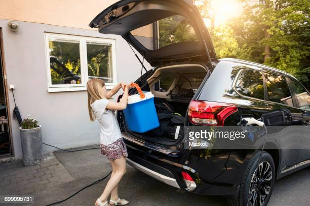 girl loading cooler in black car trunk against house - boot stock pictures, royalty-free photos & images