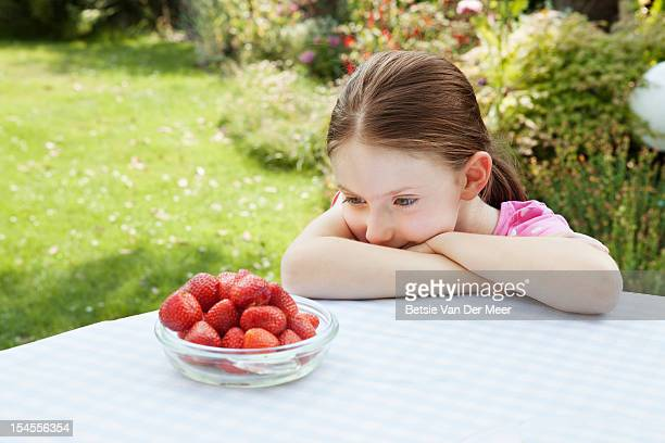 Girl looking a bowl of fresh strawberries.