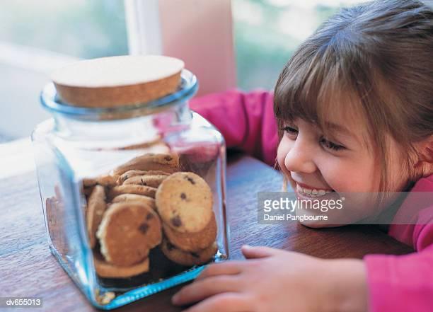 Girl Looking a Jar of Cookies