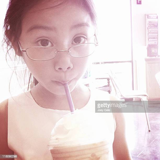 Girl looking above her glasses while drinking
