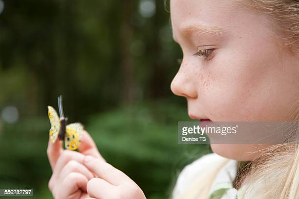 Girl looking at a butterfly