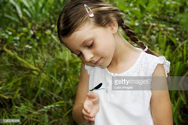 Girl looking at a dragonfly on her hand