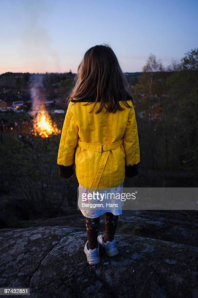 Girl looking at a fire, Sweden.