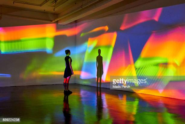 girl looking at a large scale image of projected patterns - imagination stock pictures, royalty-free photos & images
