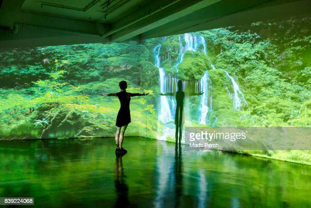 Girl looking at a large scale nature image projected on to a wall