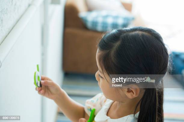 Girl looking at alphabet magnet, side view