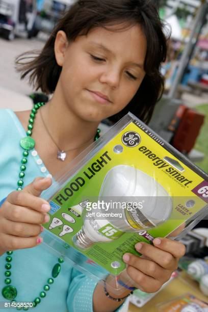 A girl looking at an energy smart light bulb at the Miami Goin' Green event