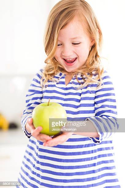 Girl (4-5) looking at apples, laughing