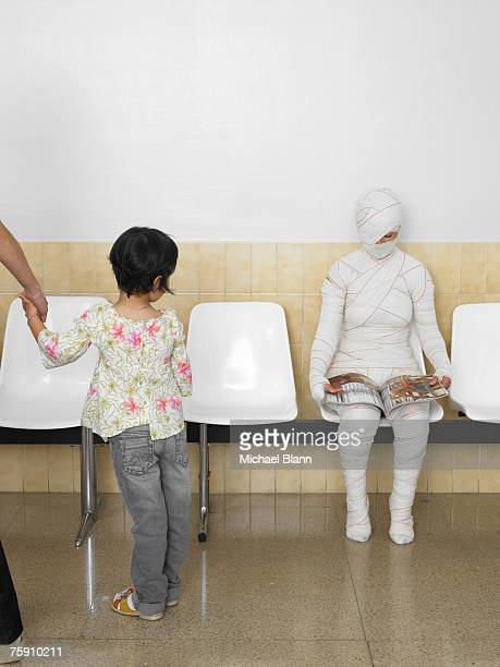 girl (5-7 years) looking at bandaged patient in waiting room - 30 34 years stock-fotos und bilder