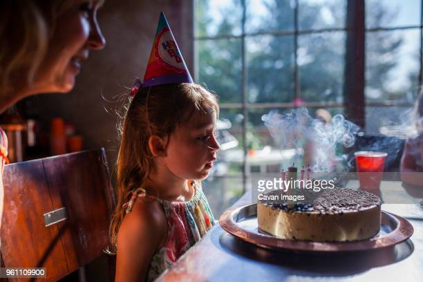 girl looking at birthday cake with mother at home - mother and daughter smoking stock photos and pictures