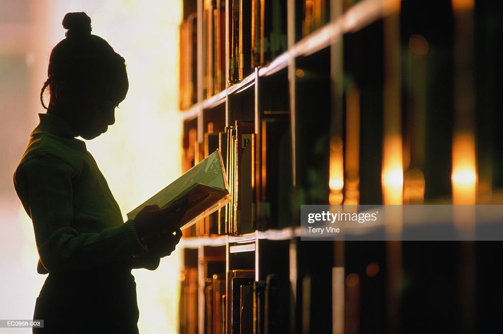 Girl (6-8) looking at book in library, silhouette : Stock Photo