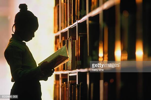 girl (6-8) looking at book in library, silhouette - education stock pictures, royalty-free photos & images