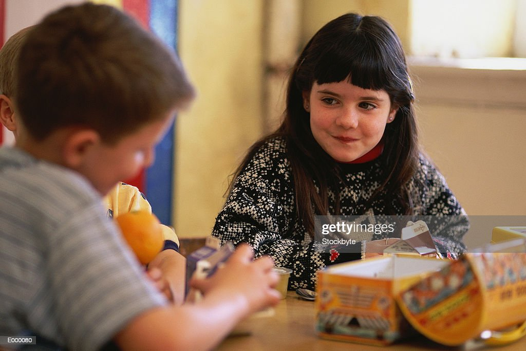 Girl looking at boy, sitting at table in lunchroom : Stock Photo