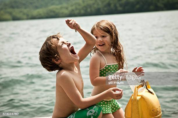 girl (5-6) looking at brother (10-12) eating raw fish - exhibitionniste photos et images de collection