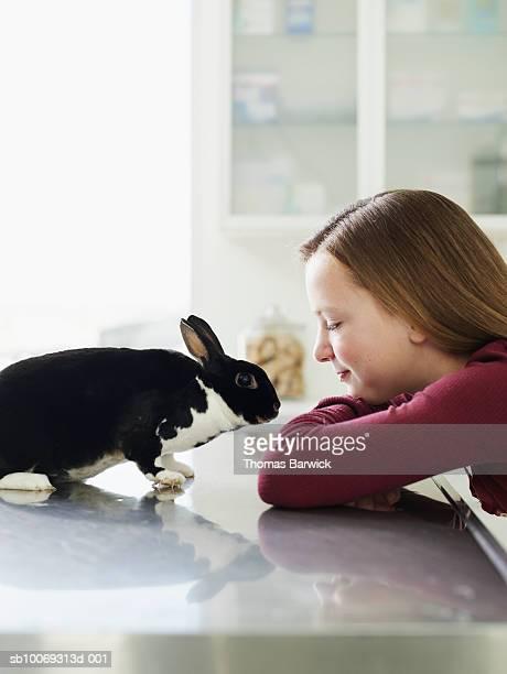 Girl (8-9) looking at bunny on exam table in veterinarian exam room