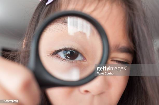 girl looking at camera through magnifying glass - zoom in stock pictures, royalty-free photos & images