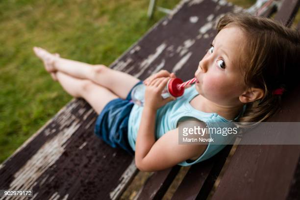 Girl looking at camera while sipping water