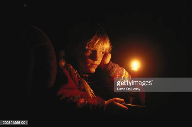Girl (6-9) looking at candlelight in dark room