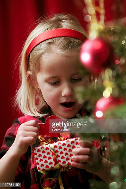 girl looking at christmas present - newpremiumuk stock pictures, royalty-free photos & images
