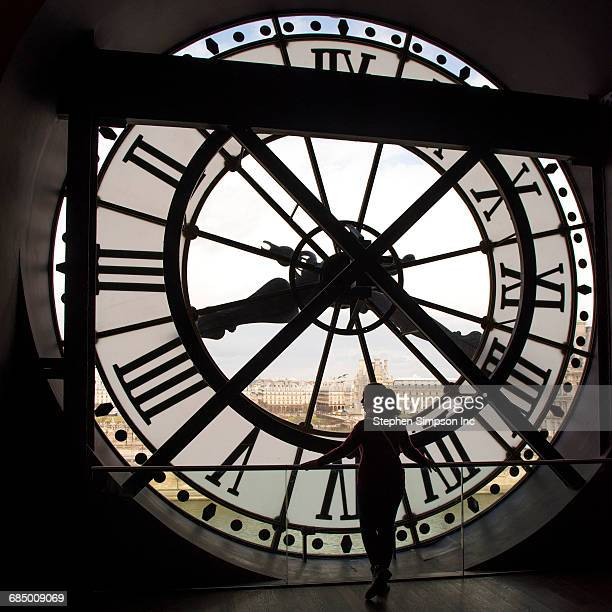 girl looking at city from behind clock - clock tower stock pictures, royalty-free photos & images