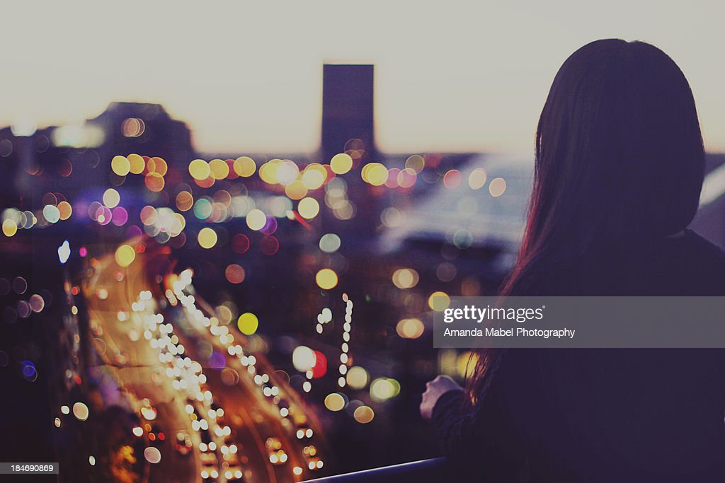 Girl looking at city night view of lights : Stock Photo