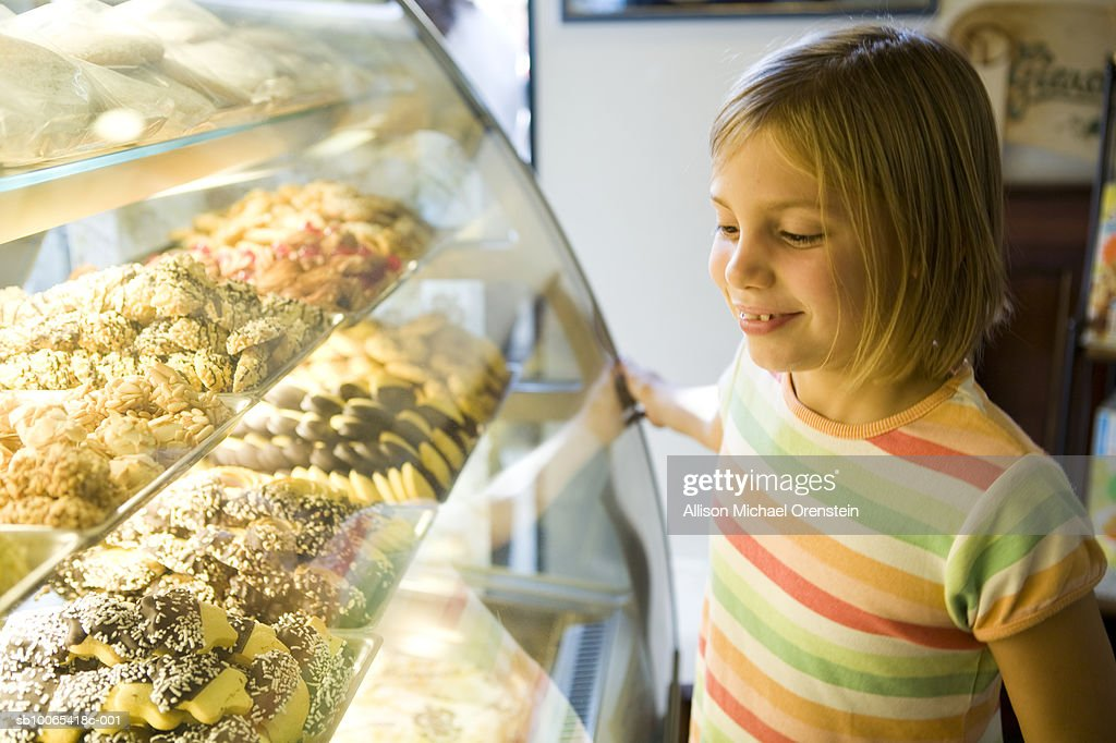 Girl (8-9) looking at cookies at bakery : Foto stock