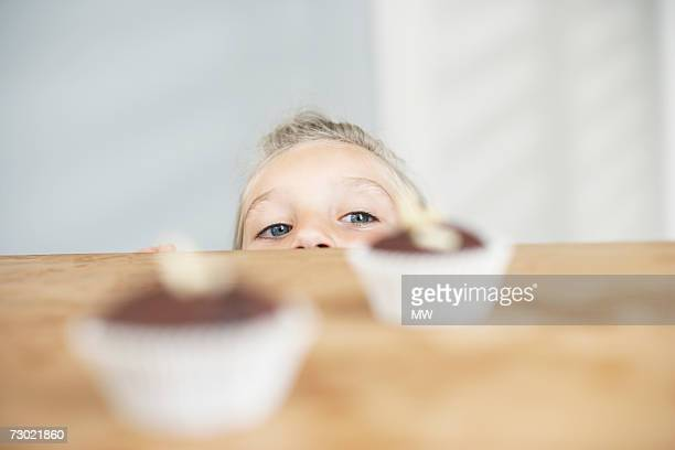 'Girl (5-7) looking at cupcakes on counter, high section'