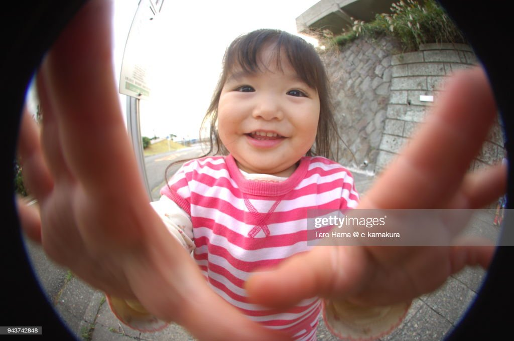 A girl looking at fish-eye lens camera in Japan : ストックフォト