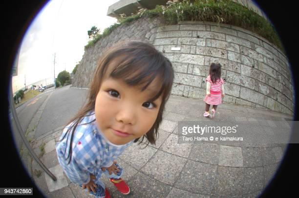 a girl looking at fish-eye lens camera in japan - fish eye foto e immagini stock