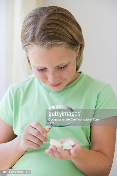 Girl (8-9) looking at flower petals through magnifying glass