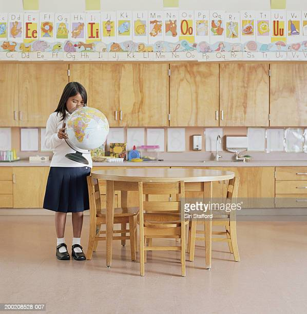 Girl (7-9) looking at globe in classroom, portrait