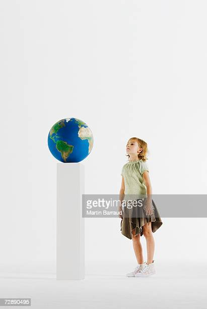 Girl (8-9) looking at globe on pedestal
