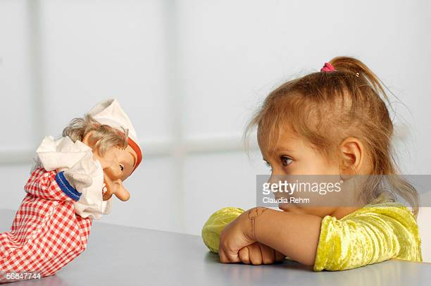 Girl (3-5) looking at glove puppet