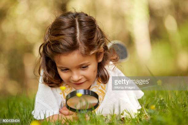Girl looking at grass through magnifying glass