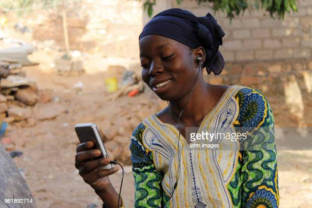 a girl looking at her phone - mali photos et images de collection
