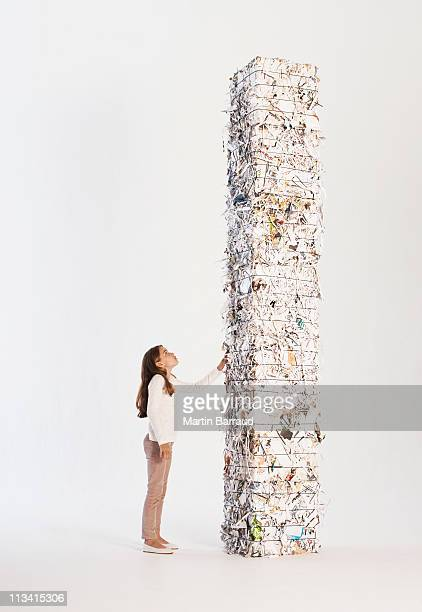 Girl looking at high stack of paper bales