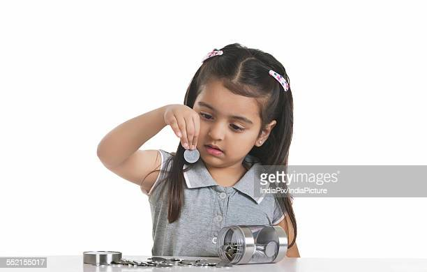 Girl looking at Indian coin against white background