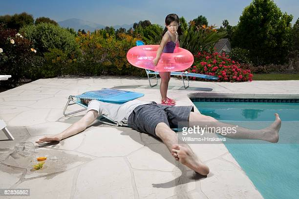 Girl looking at man in collapsed deck chair