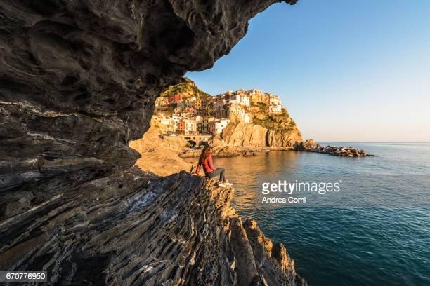 A girl looking at Manarola village from the rocks at sunset. Manarola, Cinque Terre, La Spezia, Liguria
