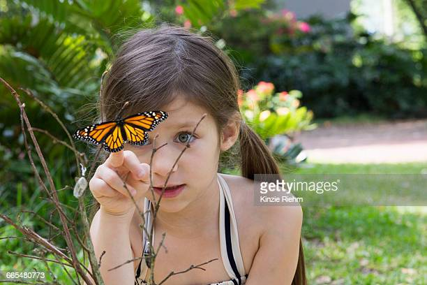 Girl looking at monarch butterfly on plant