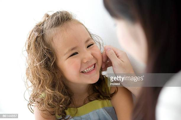 girl looking at mother, smiling - focus on background ストックフォトと画像