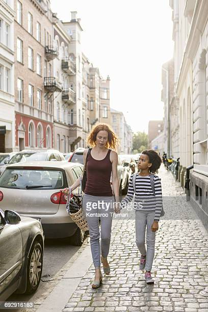 Girl looking at mother while walking on sidewalk in city