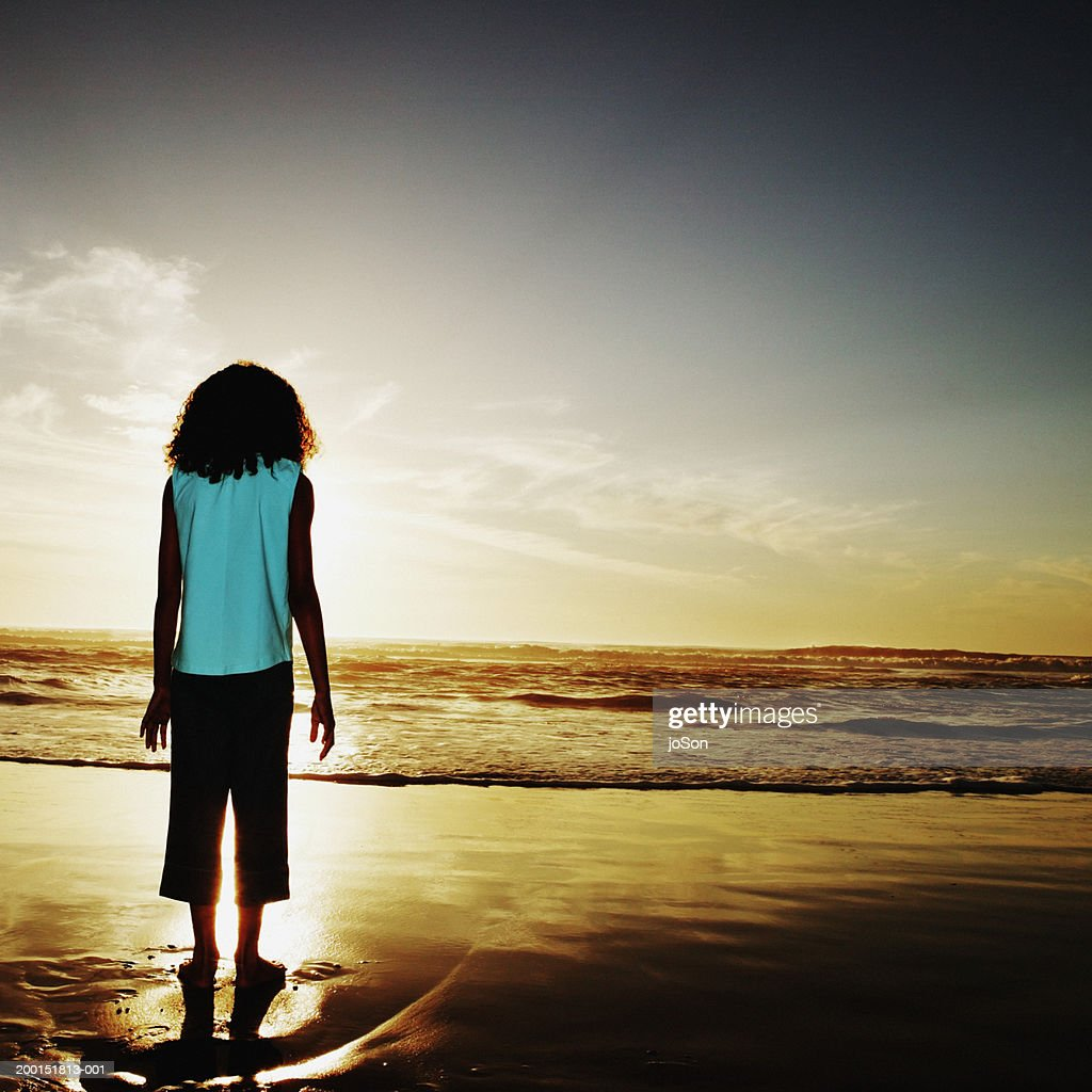 Girl Looking At Ocean Sunset Rear View Stock Photo