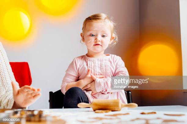 Girl looking at pastry dough while standing besides mother
