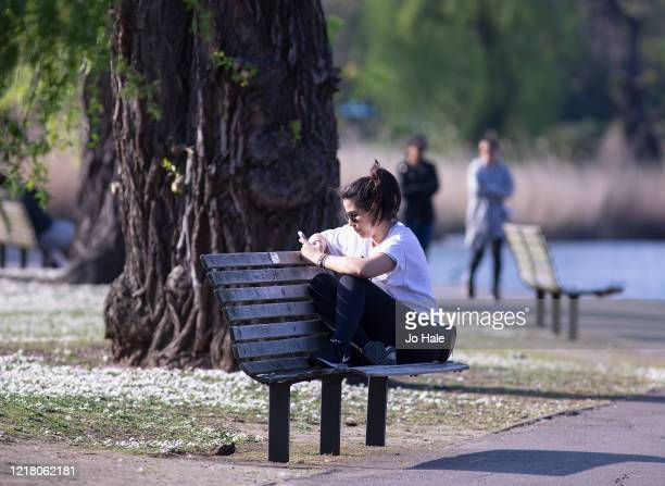 Girl looking at phone while relaxing on a bench in Regents Park Good Friday on April 10 2020 in London There have been around 70000 reported cases of...