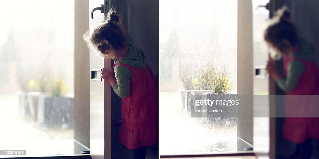 Girl Looking At Rainstorm Out The Front Door Stock Photo Getty Images