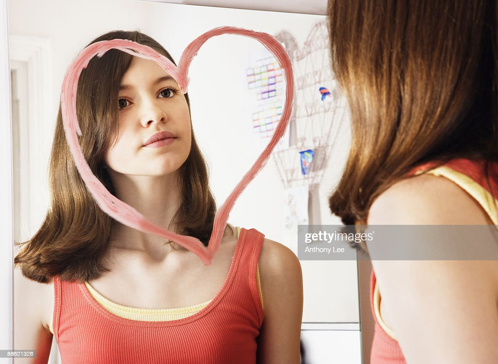 Girl looking at reflection in mirror decorated with heart-shape : Stock Photo
